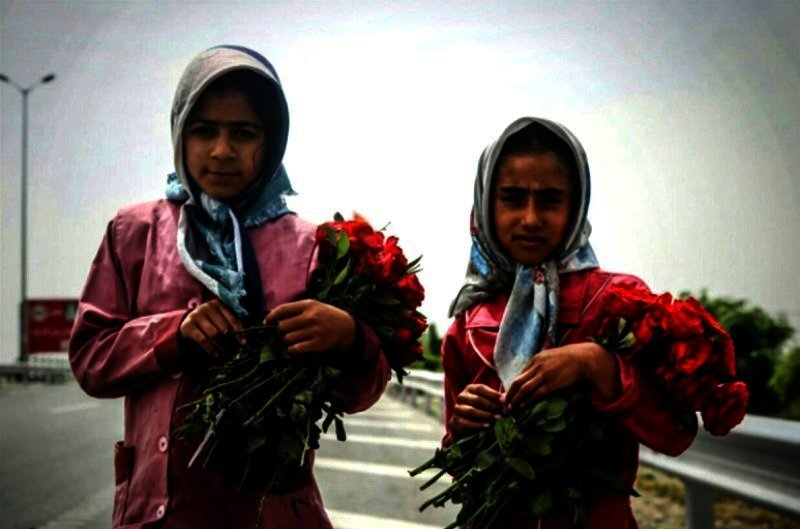 Child laborers selling flowers in Iran.